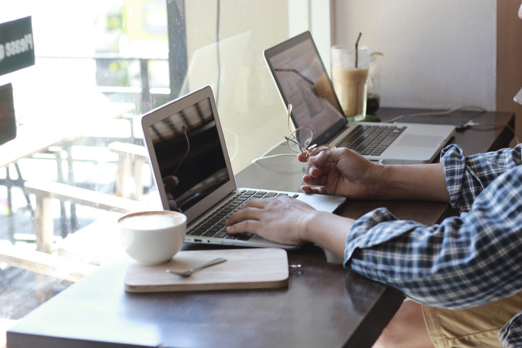 Man typing with laptop.working at coffee shop